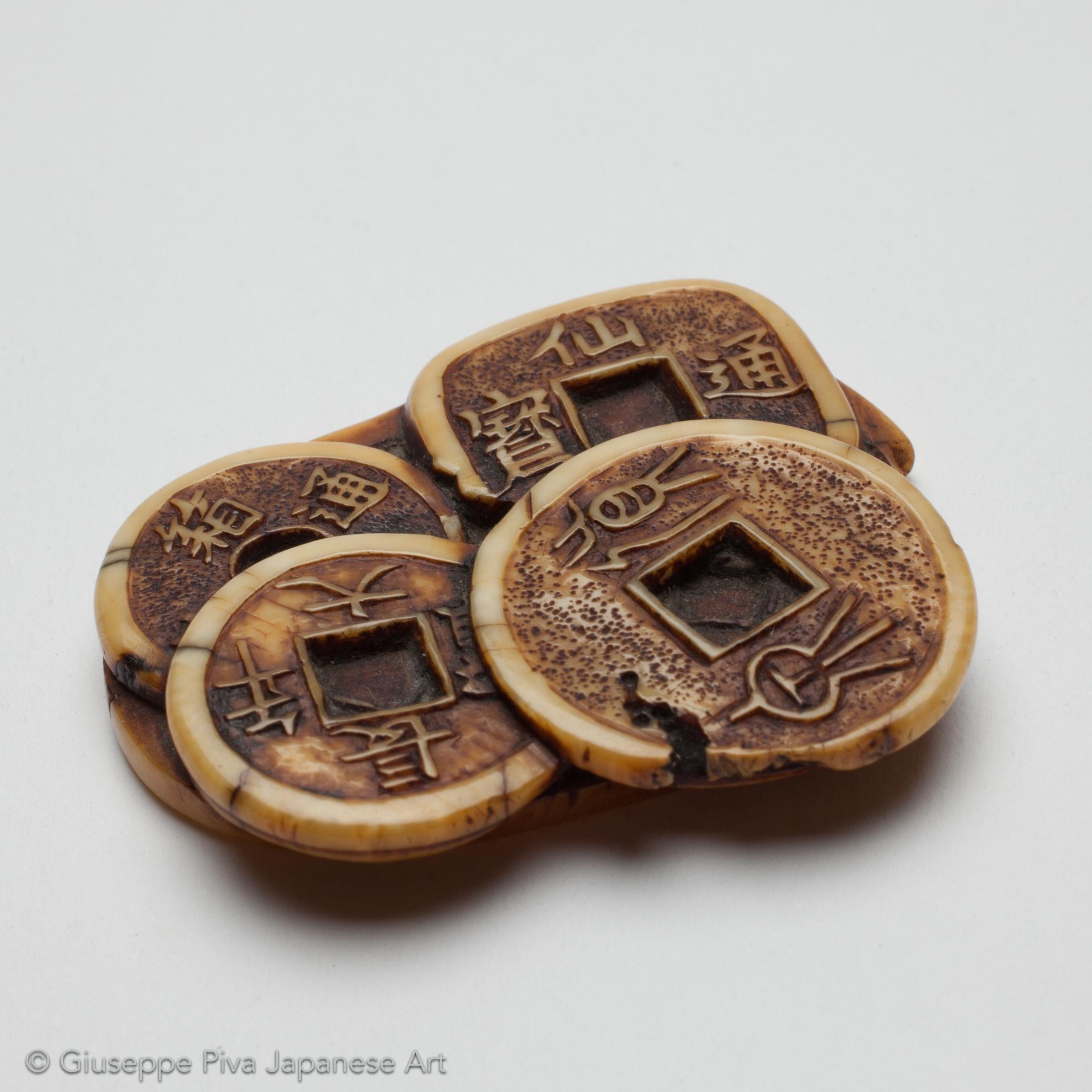 Netsuke in avorio raffigurante una pila di monete